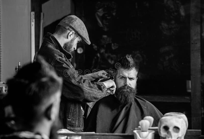 得到理发的行家客户 理发概念 称呼残酷有胡子的客户的头发的有飞剪机的理发师 理发师与 库存图片