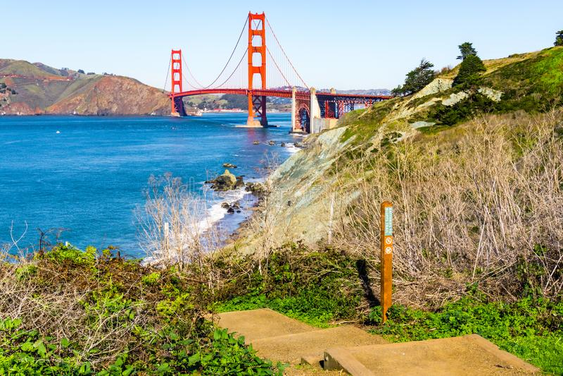 往金门海峡桥梁从沿海足迹,普雷西迪奥公园,旧金山,加利福尼亚的看法 库存图片