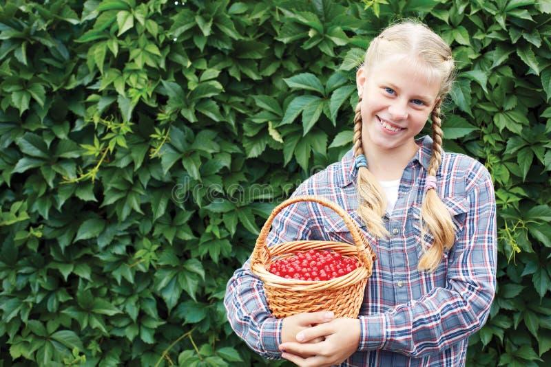 快乐的女孩在绿色墙壁的背景站立在庭院,她的手里 库存图片