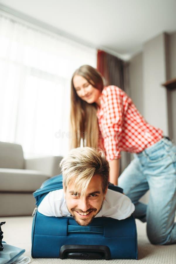 快乐的女孩包装了她的手提箱的丈夫 库存照片