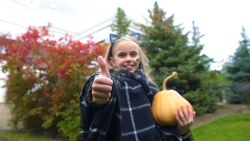快乐的女孩陈列赞许,为万圣节,秋天假日拿着杰克南瓜 库存图片