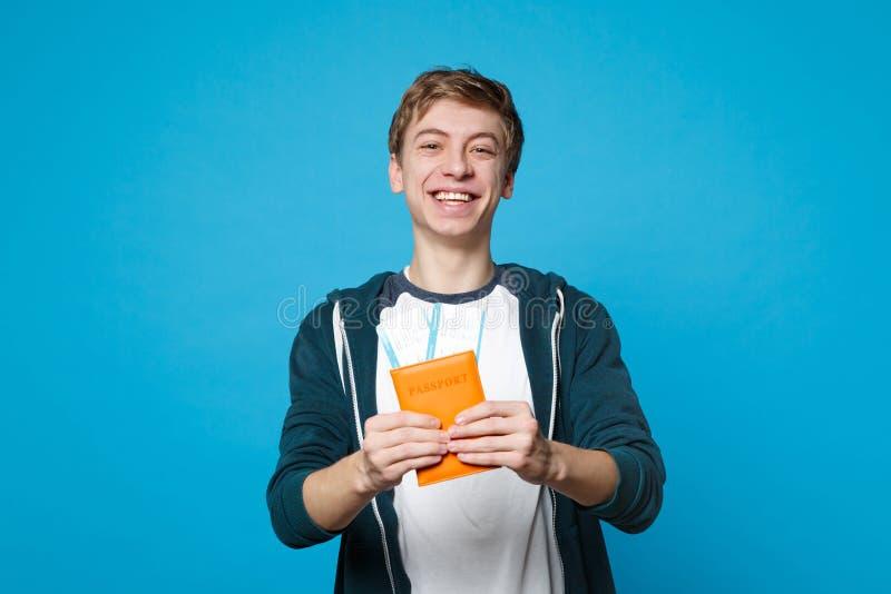 快乐的年轻人画象便服的持护照,在蓝色墙壁背景隔绝的登机牌票 图库摄影