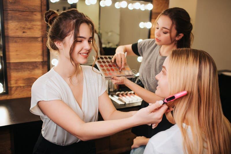 快乐的年轻美发师推力金发与夹子 她微笑 另一个女孩举行刷子和眼影膏调色板 库存图片