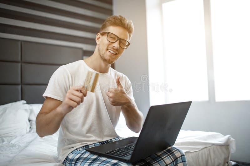 快乐的正面年轻人今天上午坐在床边缘  他在照相机和微笑看 人举行信用卡和展示 库存图片