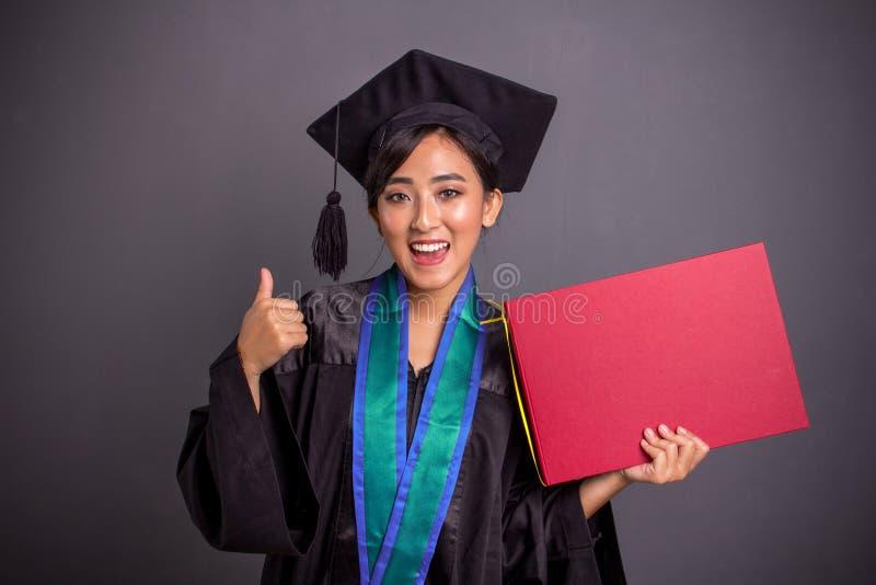 快乐的毕业的女孩赞许,当藏品招贴,在灰色背景时的画象 免版税库存照片