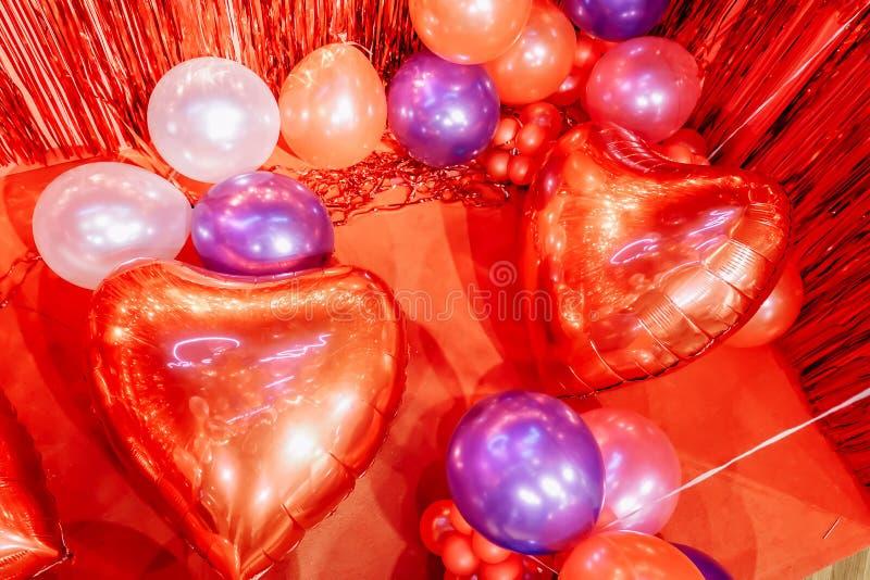 心形的箔气球在淡色红色背景的 概念亲吻妇女的爱人 节假日庆祝 免版税库存图片