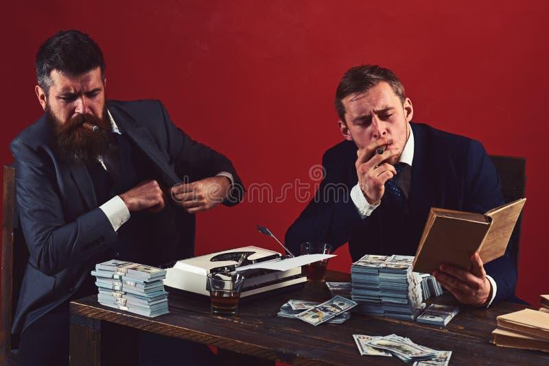 必要的信息 在事务的成功的投资 商人写财政报告,当喝和抽烟时 图库摄影