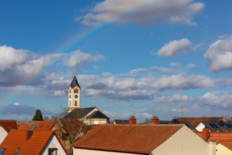 基督教会在彩虹背景中在弗兰肯塔尔德国 免版税库存图片