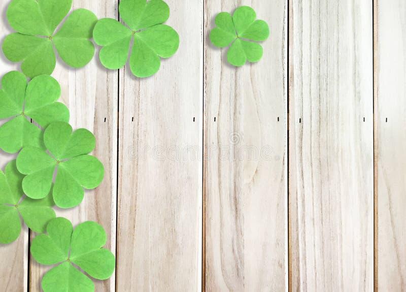 圣帕特里克的与绿色三叶草的天背景在木纹理留下顶面角落 免版税图库摄影