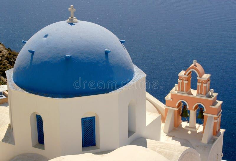 圣托里尼海岛提供在海洋的激动人心的景色从五颜六色的蓝色圆顶教会 免版税图库摄影