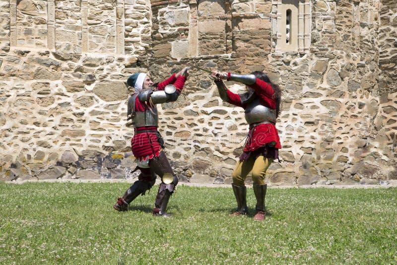 在两个勇敢的中世纪骑士之间的战斗场面在白天 库存图片