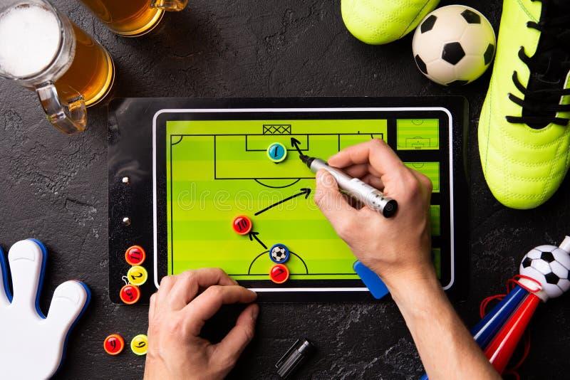 在两个杯子的照片泡沫的啤酒、桌橄榄球和人的手顶部,画的计划 免版税库存图片