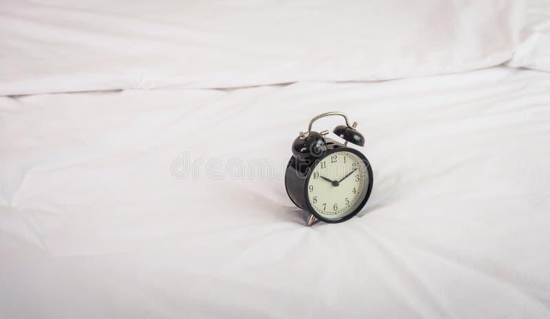 在上午8点的黑闹钟在床上 免版税图库摄影