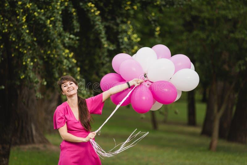 在与桃红色气球的桃红色礼服戏剧weared的年轻白种人女孩 免版税库存照片