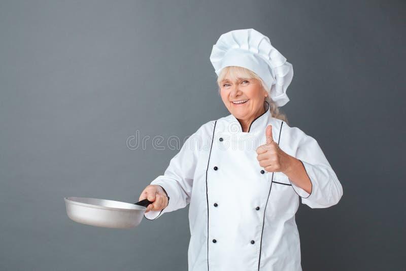 在与烹调晚餐陈列赞许微笑的煎锅的灰色隔绝的资深妇女厨师演播室身分愉快 免版税图库摄影