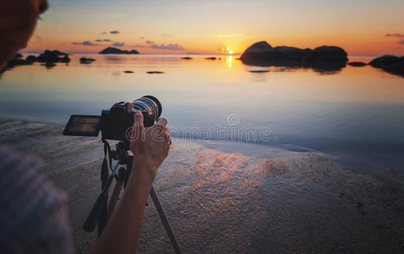 在三脚架海滩海日落的照片照相机 爱好旅行摄影概念 美丽的横向海运 免版税库存图片