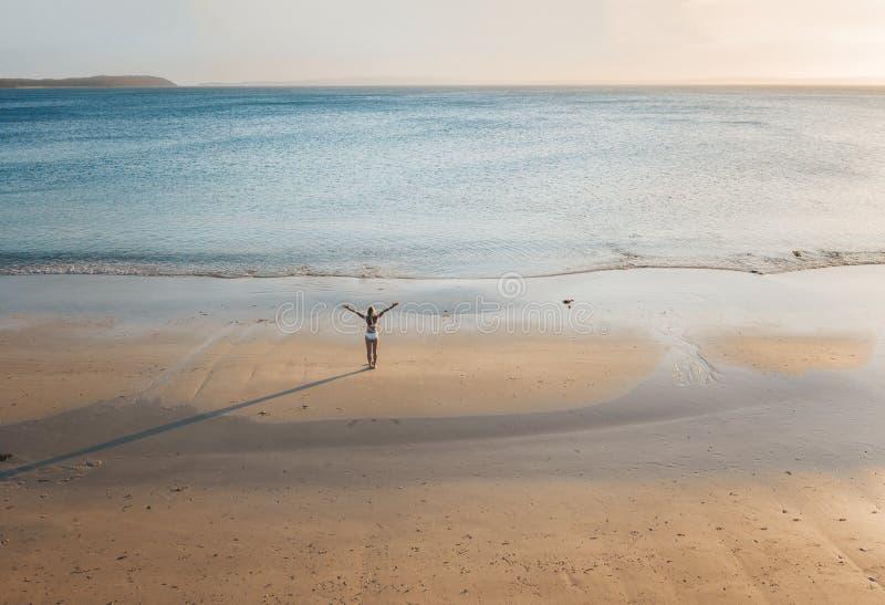 在一个偏僻的海滩的女性立场在日落 库存照片
