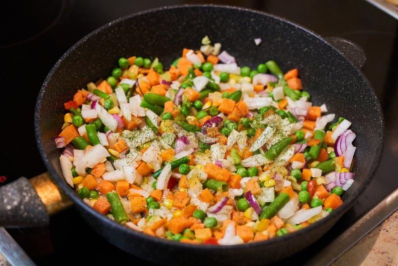 在一个平底锅的菜混合物在一个玻璃陶瓷火炉 库存图片