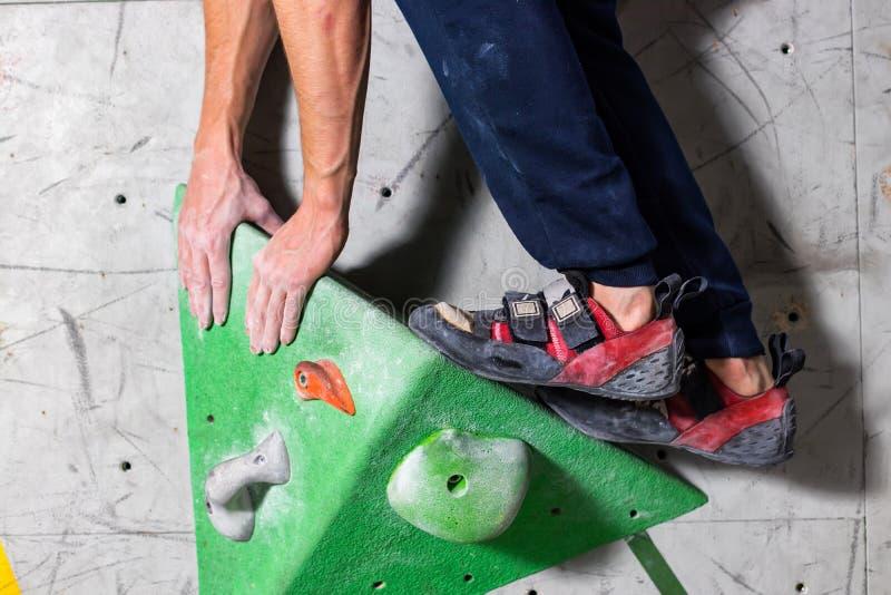 在一个微小,不足的圈套立场的岩石鞋子与袜子的技巧在特写镜头的在上升的墙壁上在屋子里 库存图片
