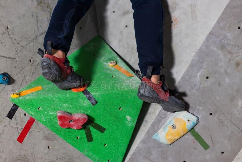 在一个微小,不足的圈套立场的岩石鞋子与袜子的技巧在特写镜头的在上升的墙壁上在屋子里 免版税库存照片