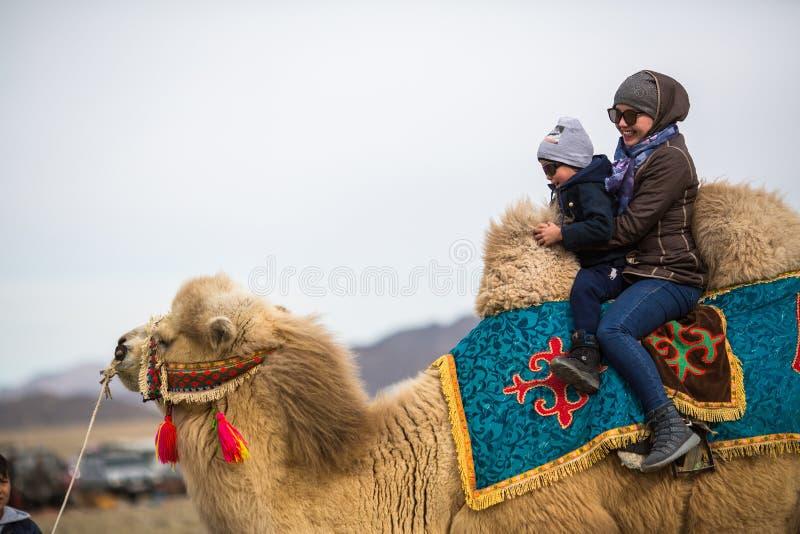 在一个地方假日期间,地方哈萨克人妇女在骆驼乘坐孩子 库存图片