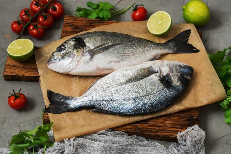 在一个切板的新鲜的dorado鱼有石灰、蕃茄和绿色的 免版税库存照片
