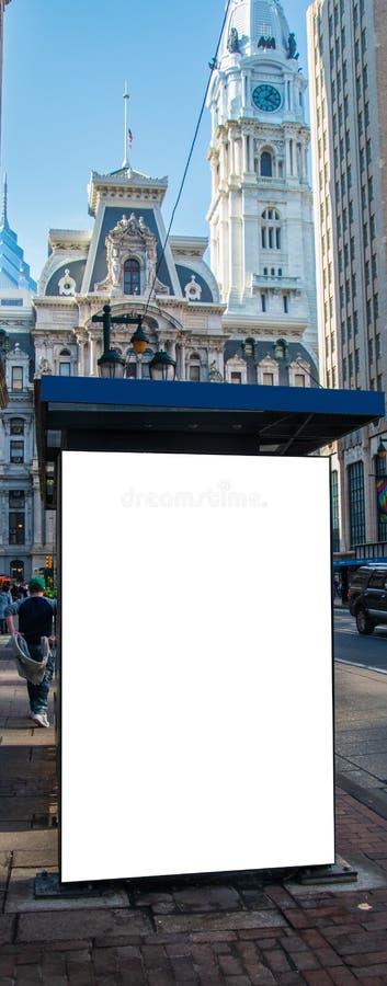 在一个公车候车厅一边的空白的白色标志在有一个大老历史建筑的一条城市街道上在背景中 库存照片