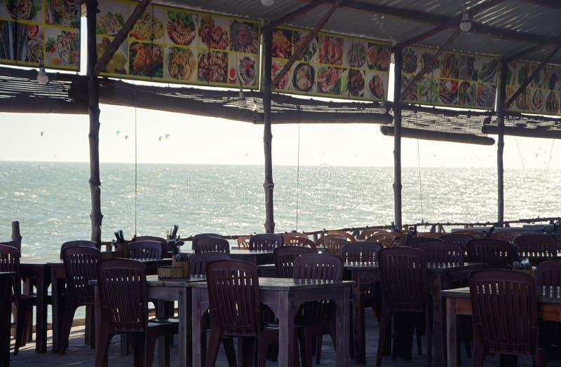 在一个咖啡馆的表在海滩的一个机盖下 从咖啡馆的看法在太平洋 库存图片