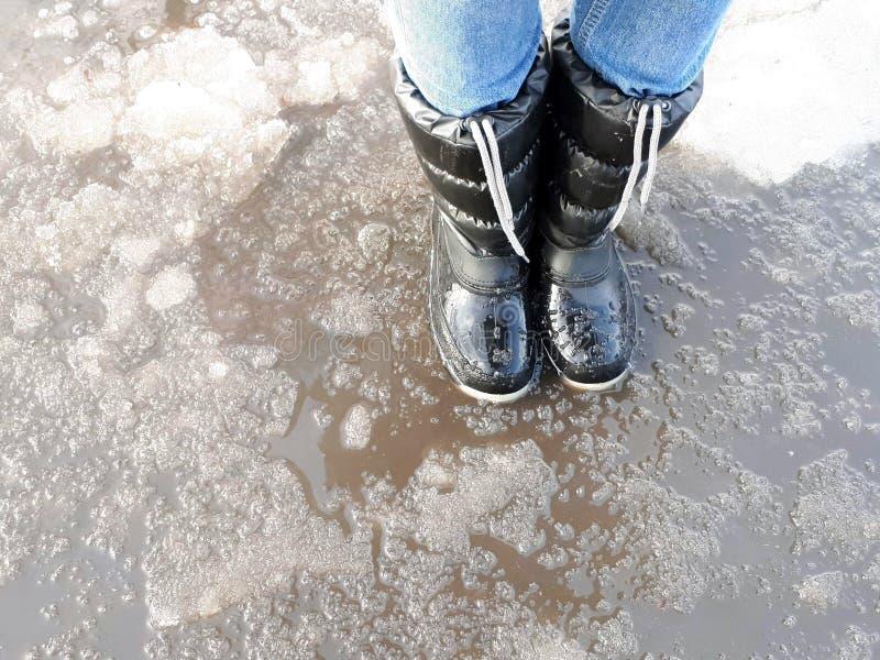 在一个水坑在早期的春天,解冻的概念的妇女的黑胶靴 免版税库存照片
