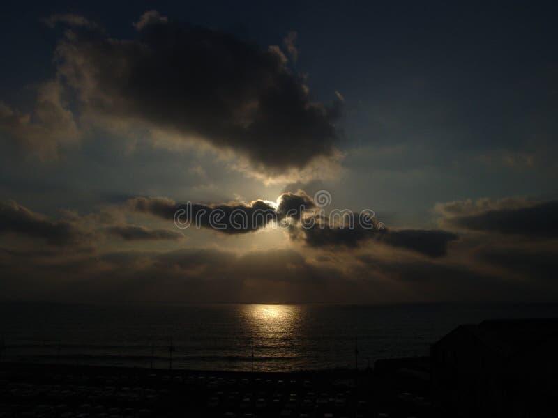 在一个海滩的多云日落与在黑暗的一个大停车场停车场许多  库存图片