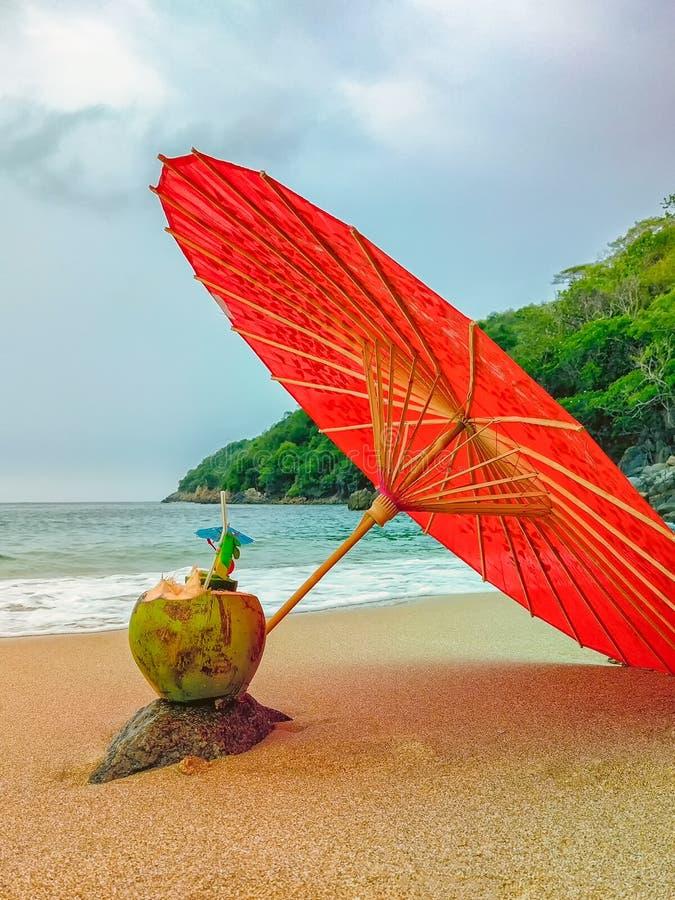 在一个海滩的皮纳colada热带饮料饮料在一把红色伞下 免版税库存照片