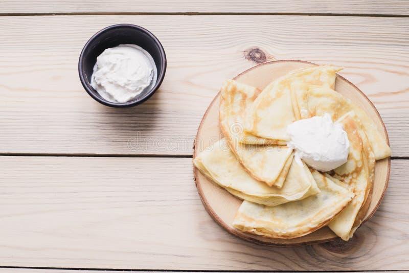 在一个木立场的俄国稀薄的薄煎饼由与酸性稀奶油的自然木头制成 Maslenitsa是Maslenitsa食物节日 免版税图库摄影