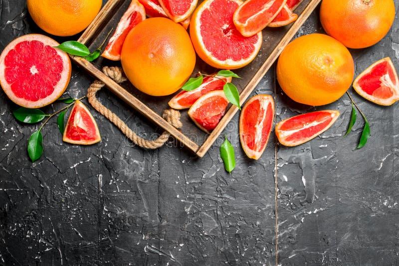 在一个木盘子的成熟葡萄柚 免版税库存图片