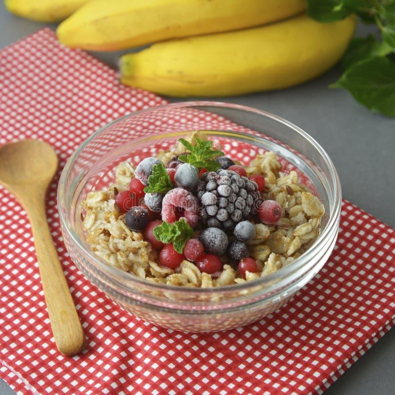 在一个碗的健康早餐有oatmeals的,冷冻莓果,新鲜的草莓,薄菏 燕麦粥用果子 方形的图象 库存照片