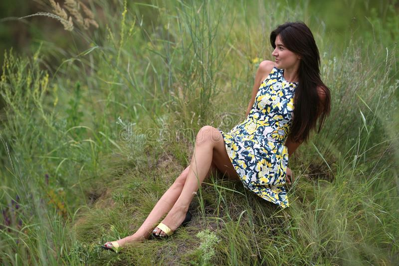 在一个绿色山沟,有长的棕色头发的一个年轻亭亭玉立的俏丽的女孩的夏天步行在一件黄色礼服sundress,享有生活 图库摄影