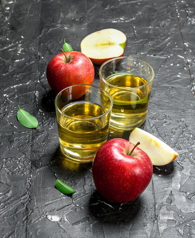 在一个玻璃瓶子的苹果汁用在箱子的新鲜的苹果 免版税库存图片