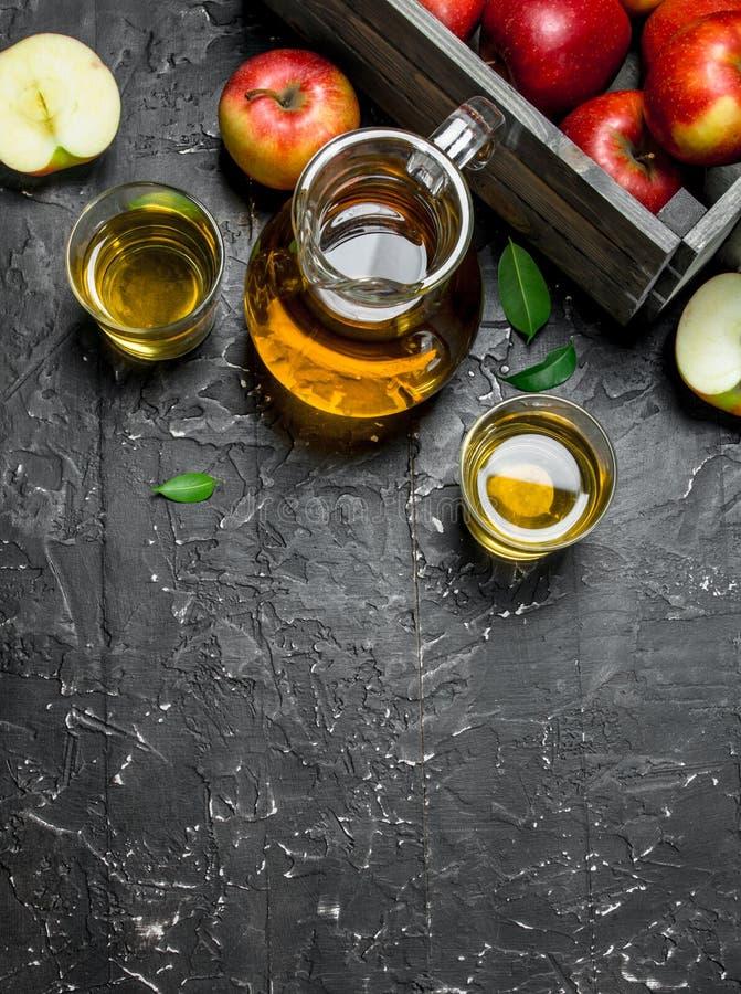 在一个玻璃瓶子的苹果汁用在箱子的新鲜的苹果 免版税图库摄影