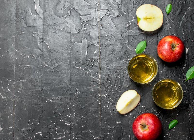 在一个玻璃瓶子的苹果汁用在箱子的新鲜的苹果 免版税库存照片