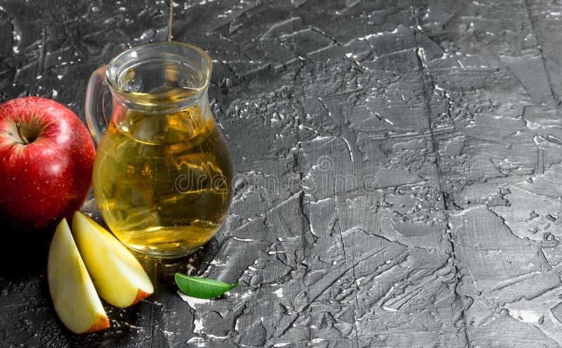 在一个玻璃瓶子的苹果汁用红色新鲜的苹果 库存图片