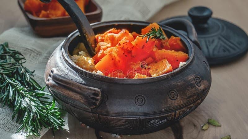 在一个煎锅切的水多的橙色南瓜的油炸物用麦子谷物和用在泥罐的乡村模式的香料 概念  库存照片