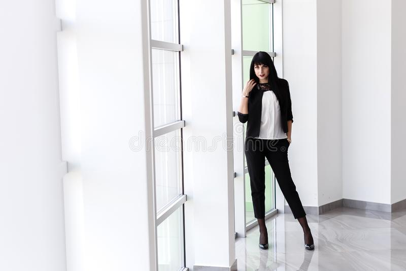 在一个黑西装身分打扮的年轻可爱的严肃的深色的妇女在窗口附近在办公室,看照相机 免版税库存图片