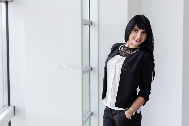 在一个黑西装身分打扮的年轻可爱的愉快的深色的妇女在窗口附近在办公室,微笑,看 免版税库存照片