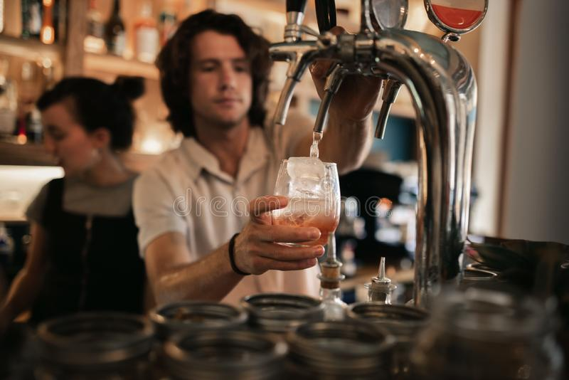 在一个酒吧柜台后的侍酒者混合的饮料在晚上 免版税库存照片