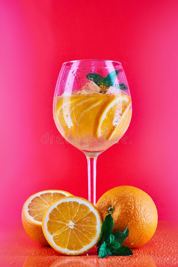 在一个酒杯的橙色鸡尾酒用在红色,珊瑚背景的薄菏用桔子 免版税图库摄影
