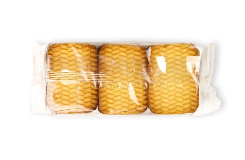 在一个透明包裹的金黄曲奇饼 关闭 在空白背景 免版税图库摄影