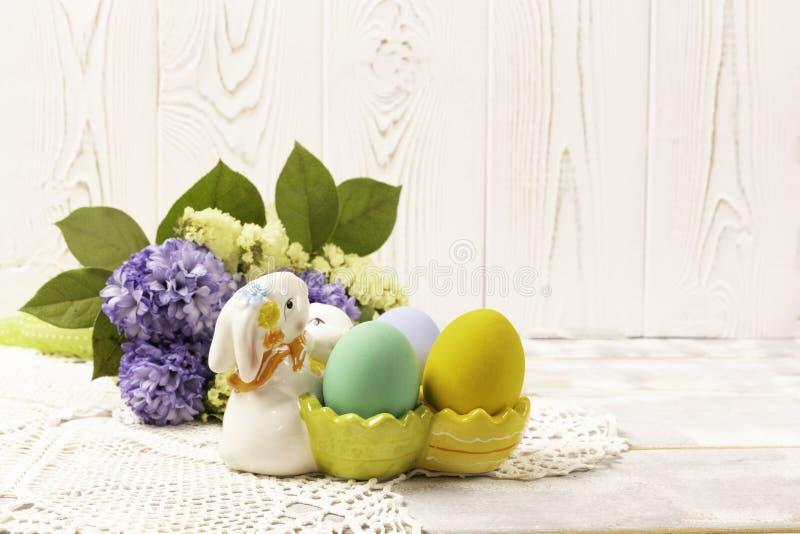 在一个陶瓷兔子立场和春天花束的五颜六色的复活节彩蛋与在一块美丽的被编织的餐巾的淡紫色和黄色花  免版税库存照片