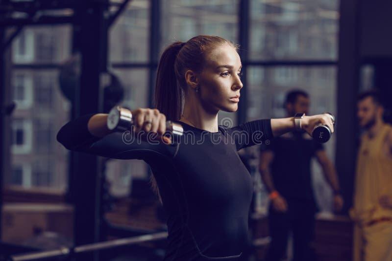 在一件黑运动服打扮的苗条少女做着与哑铃的锻炼在与许多的现代健身房体育 库存照片