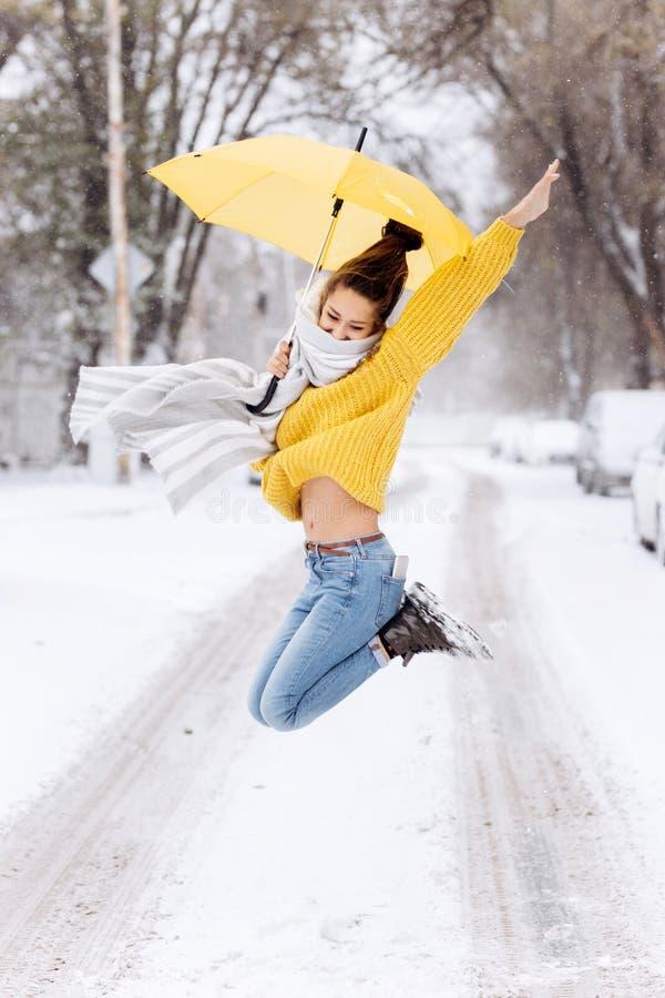 在一件黄色毛线衣、牛仔裤和一条白色围巾打扮的愉快的深色头发的女孩跳与在多雪的一把黄色伞 库存照片