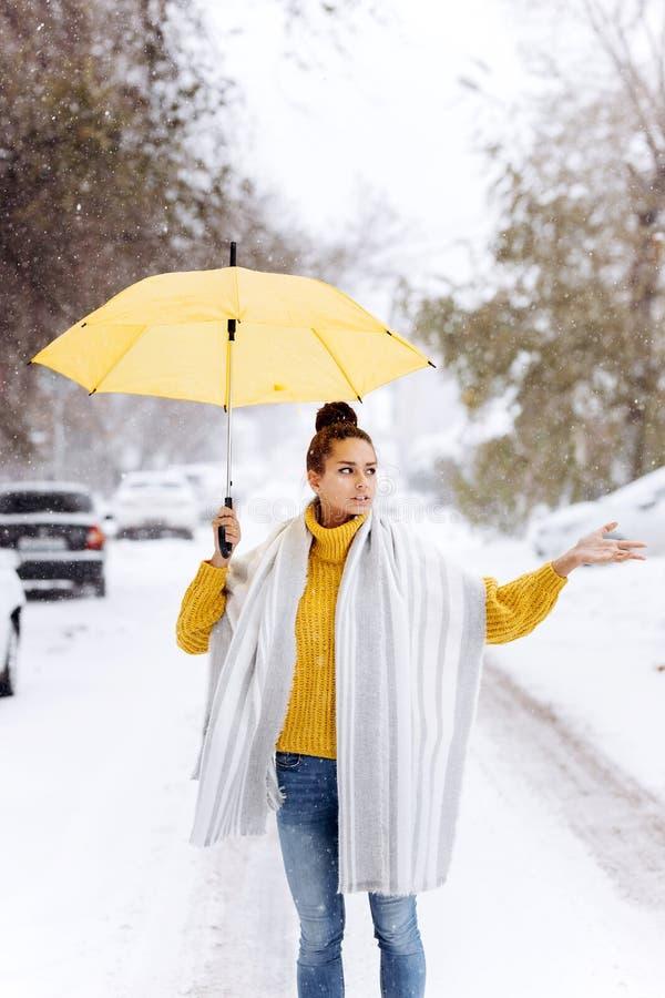 在一件黄色毛线衣、牛仔裤和一条白色围巾打扮的美丽的深色头发的女孩站立与在a的一把黄色伞 库存图片