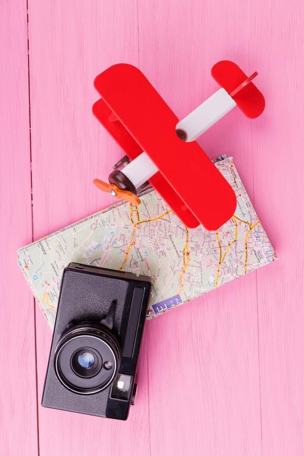 在一台桃红色背景照相机的特写镜头,飞机,地图 库存图片
